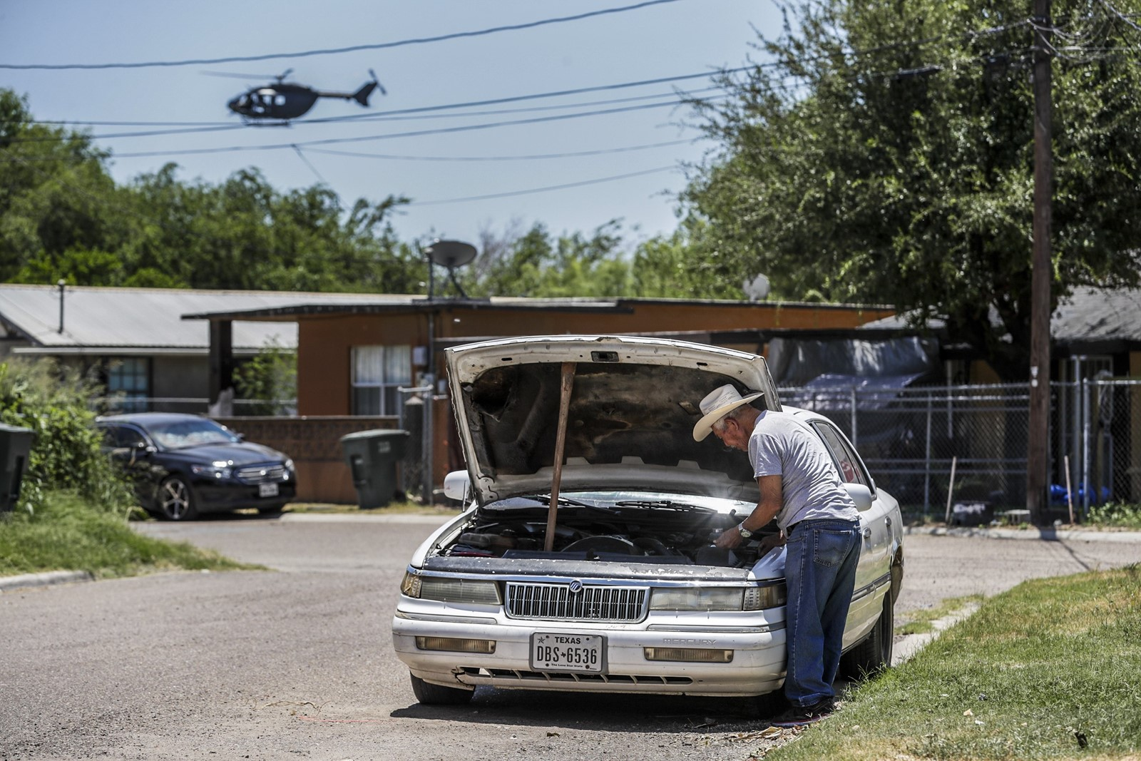 Juan Silva of Roma, Texas, works on a car as a Border Patrol helicopter searches for immigrants in the town along the Rio Grande. — Photograph: Robert Gauthier/Los Angeles Times.
