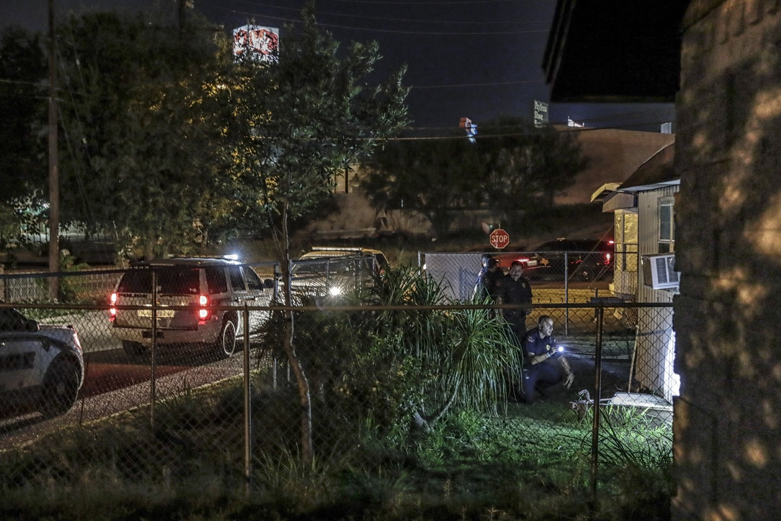 Police in Roma help Border Patrol agents search for a migrant underneath a mobile home. In the town of 11,400 residents, immigrants appear just about anywhere — hiding in carports, trees, church pews, storm drains and department store clothes racks. — Photograph: Robert Gauthier/Los Angeles Times.