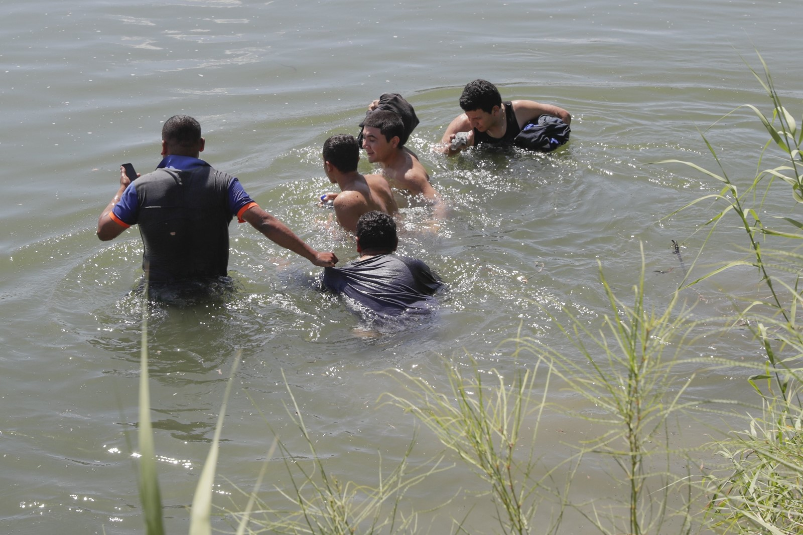 A smuggler leads migrants away from the Rio Grande riverbank on the U.S. side. They were fleeing from agents who found them hiding in reeds. — Photograph: Robert Gauthier/Los Angeles Times.