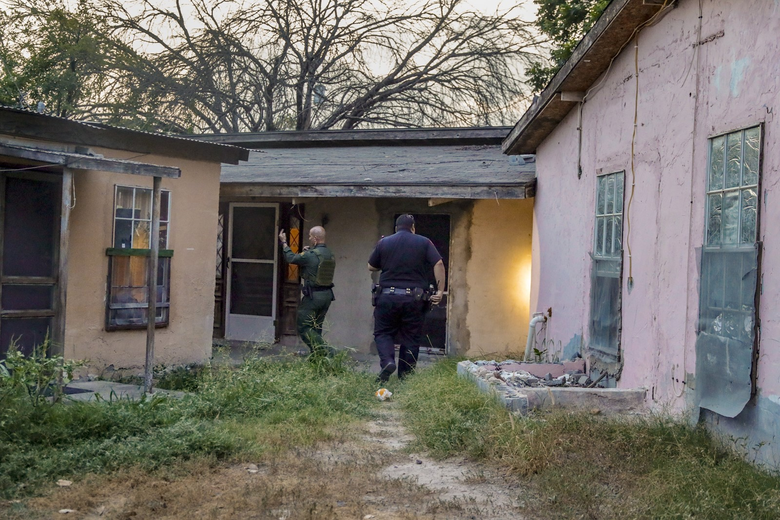 A Border Patrol agent and police officer in Roma, Texas, search the border town's so-called pink apartments, where they would detain men suspected of illegal immigration. Sandra Garcia said her family, which owns the complex, does not smuggle migrants. — Photograph: Robert Gauthier/Los Angeles Times.