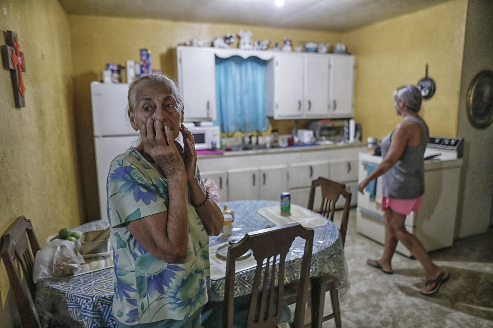 "Cristina De La Cruz, 82, watches as her daughter Maria Guadalupe Rios prepares dinner. ""You can't tell who's who,"" Rios said of neighbors. — Photograph: Robert Gauthier/Los Angeles Times."