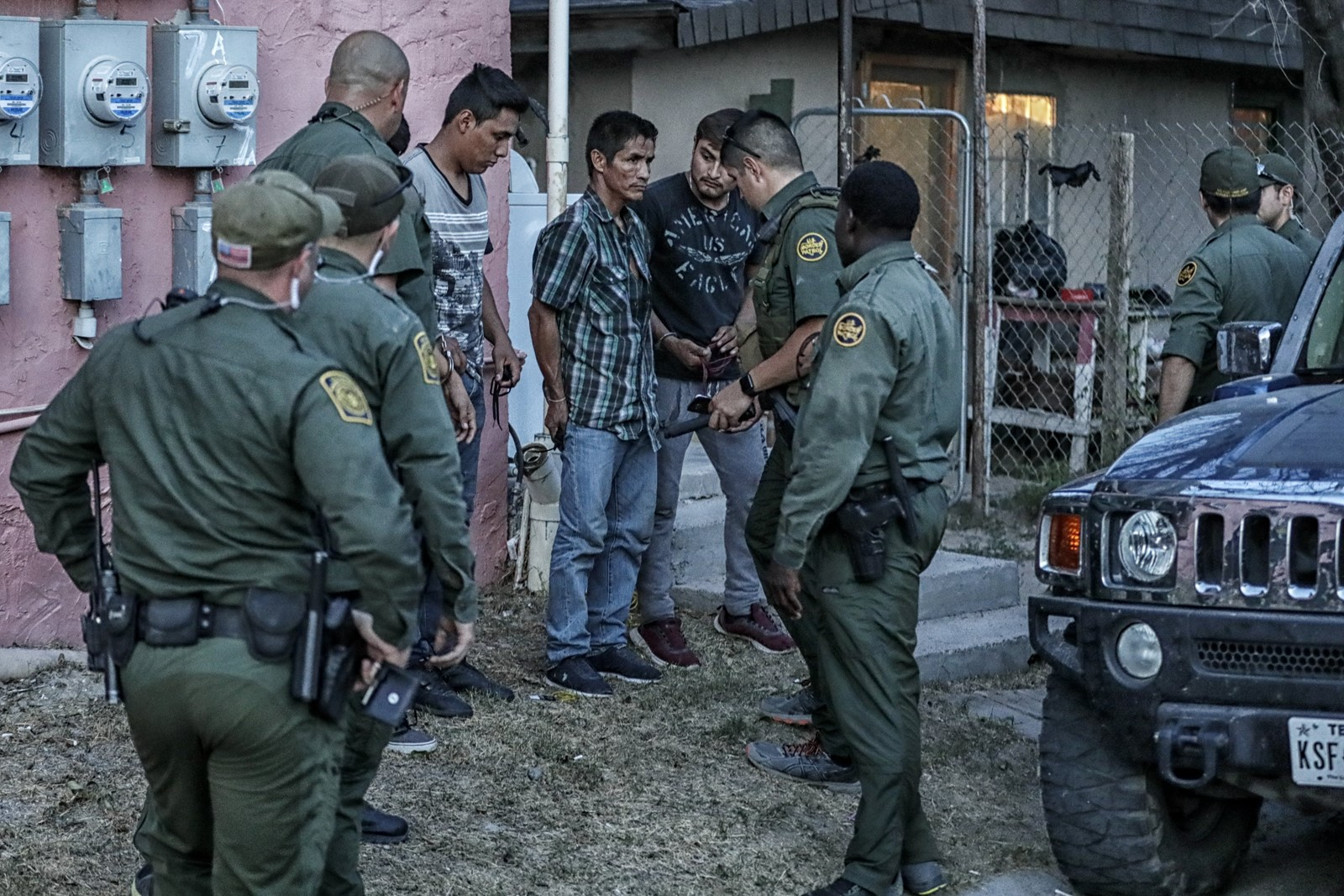 Border Patrol agents detain men at the pink apartments. Opinion of the Border Patrol is split in Roma; in the colonia, residents distrust agents. — Photograph: Robert Gauthier/Los Angeles Times.