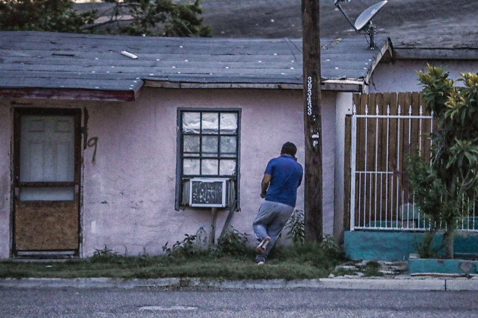 Appearing damp and lost, the man dashes toward colonia De La Cruz's pink apartments — a complex reputed by some to be a safe house for migrants. — Photograph: Robert Gauthier/Los Angeles Times.