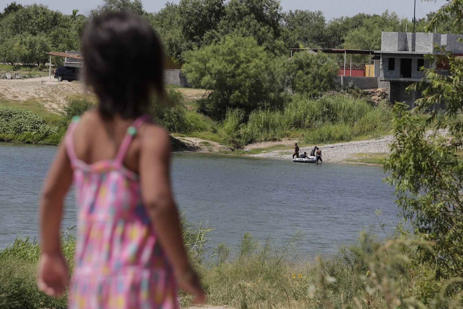 """They're in the water!"" cried Brianna Loera, 3, as immigrants on the Rio Grande retreat to Mexico after Border Patrol agents stopped them. ""Tell them bye,"" the girl's grandmother said. — Photograph: Robert Gauthier/Los Angeles Times."