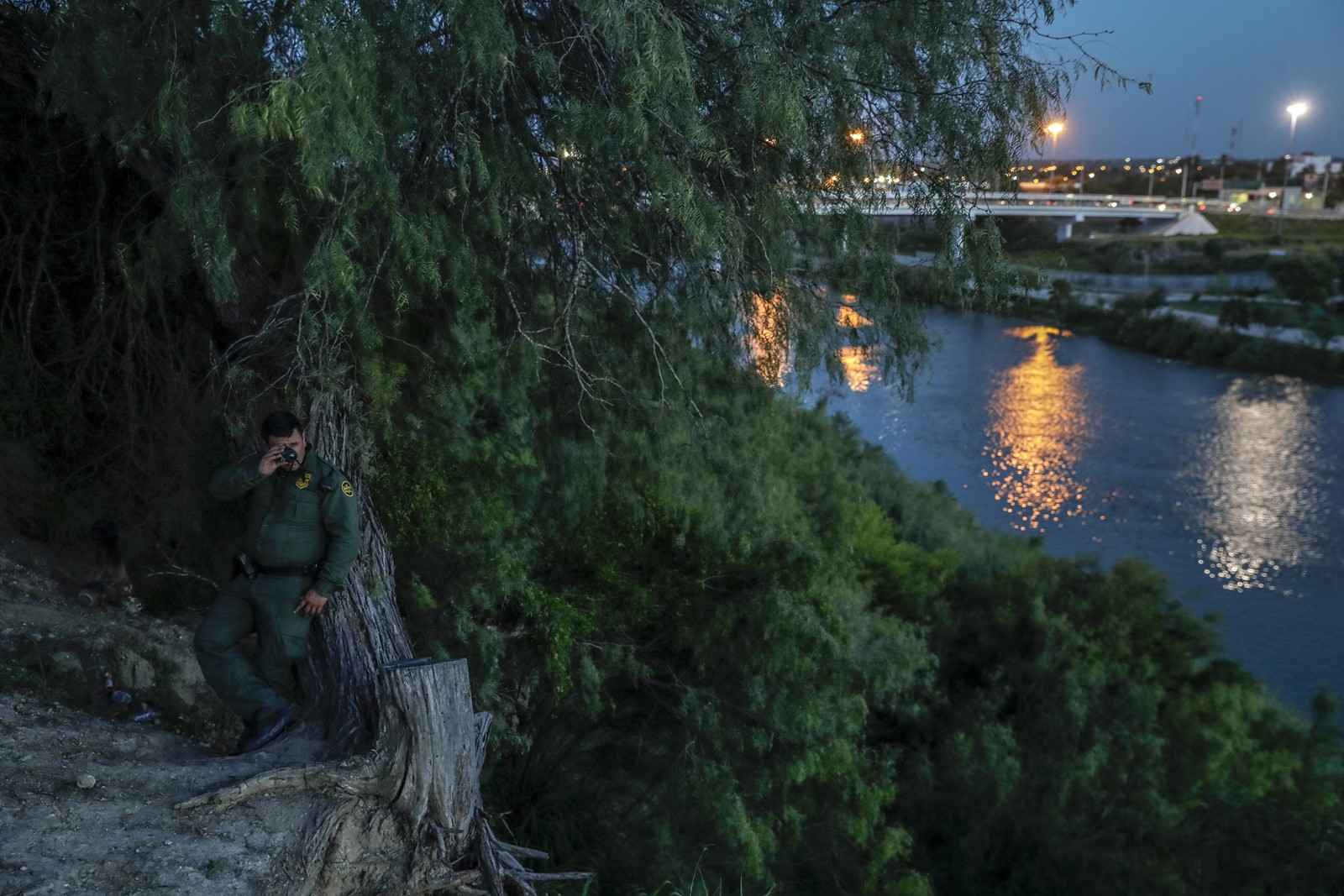 Border Patrol agent Joel Zavala looks across the Rio Grande in search of immigrants and smugglers trying to enter the United States from Mexico. Nestled among trees, he is hidden from the sight of lookouts posted hundreds of yards away across the river. — Photograph: Robert Gauthier/Los Angeles Times.