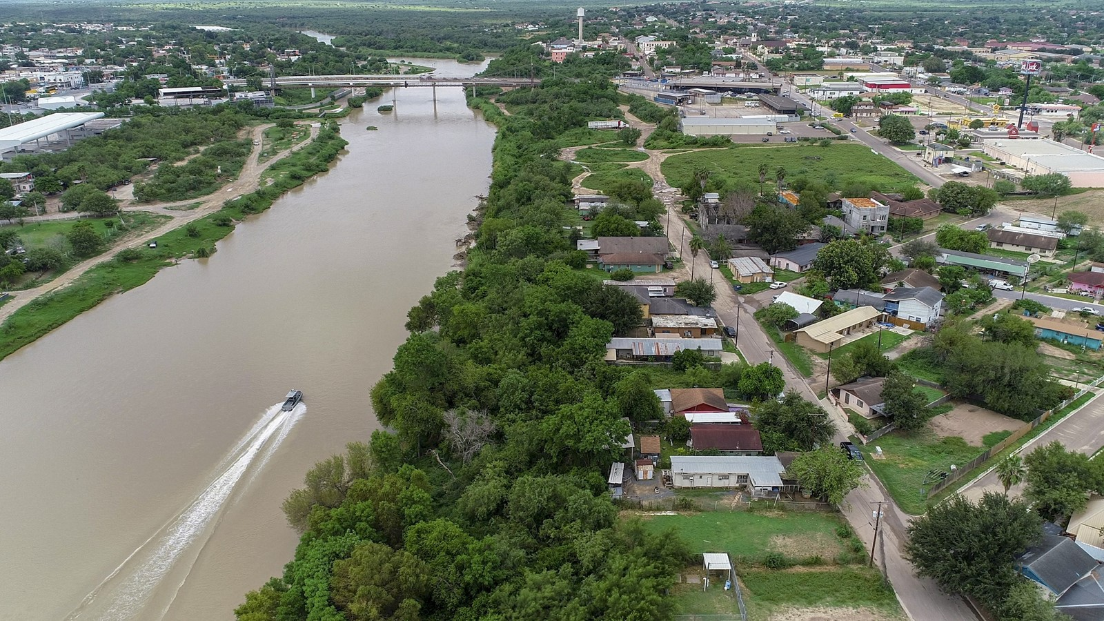 A Border Patrol boat travels the Rio Grande near the De La Cruz neighborhood of Roma, Texas. — Photograph: Robert Gauthier/Los Angeles Times.
