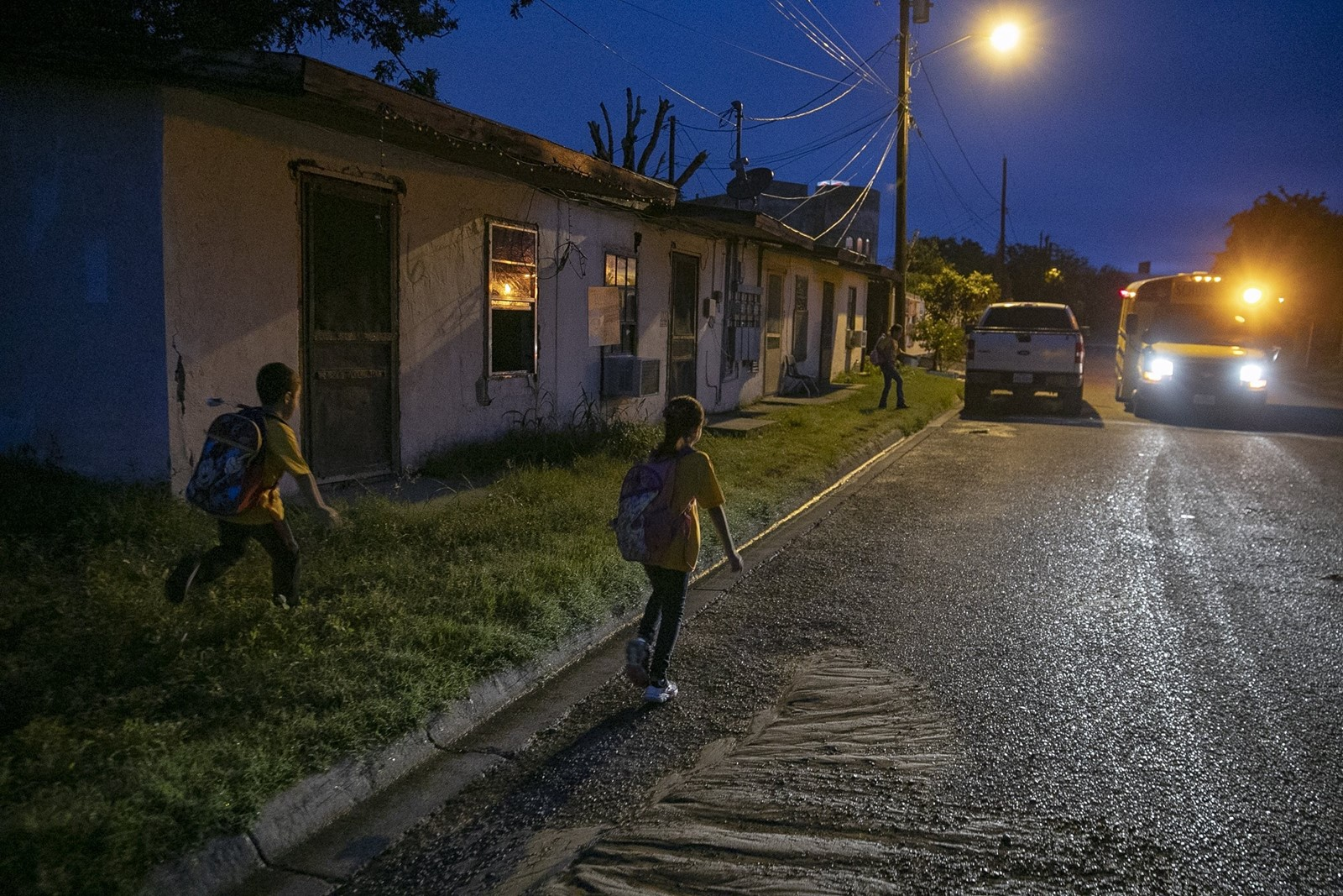 Children run to a school bus in the colonia. Some locals consider the wall a vital safeguard; others see it as a wasteful stunt. Most wish the government would be more forthright about plans. — Photograph: Robert Gauthier/Los Angeles Times.