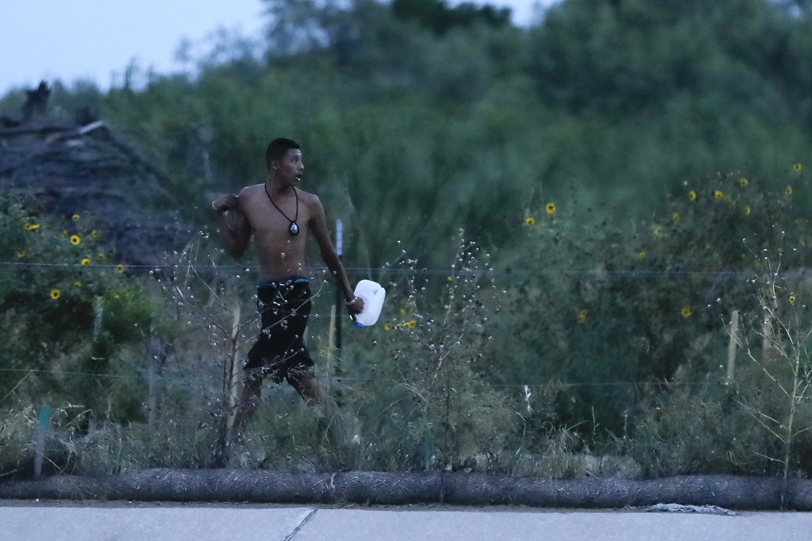 A smuggler runs along the outskirts of colonia De La Cruz in Roma after escorting a group of migrants across the Rio Grande. The riverside town is a hot spot for illegal immigration. — Photograph: Robert Gauthier/Los Angeles Times.