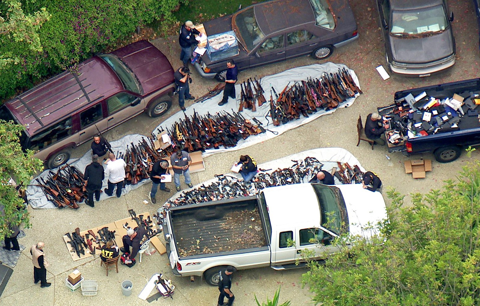 Investigators from the federal Bureau of Alcohol, Tobacco, Firearms and Explosives and the LAPD inspect a cache of weapons seized from a Bel-Air mansion. The sheer number of guns unnerved neighbors. — Photograph: KCBS/KCAL.